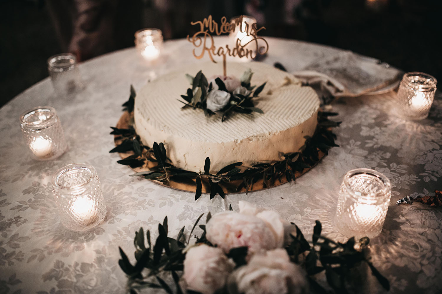 The wedding cake was traditional, covered with white blooms and greenery