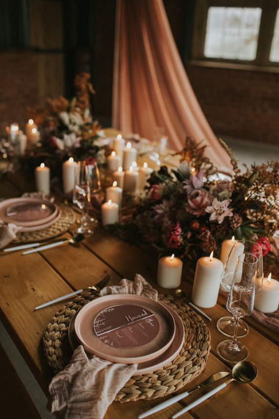 The wedding tablescape was done with woven chargers, linen napkins, candles and beautiful pink blooms