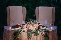 09 a dramatic and glam sweetheart table with bright blooms, greenery and candles looks very refined and chic
