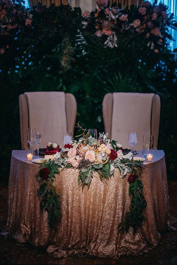 a dramatic and glam sweetheart table with bright blooms, greenery and candles looks very refined and chic