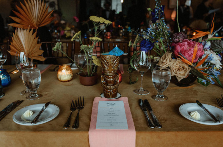 The tables were decorated in a whimsy way, with bright blooms, candles, colored fronds and bright napkins