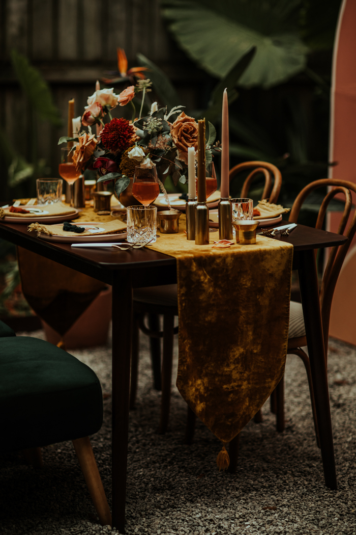 The wedding tablescape was done with a mustard velvet table runner, colored candles and bold fall blooms