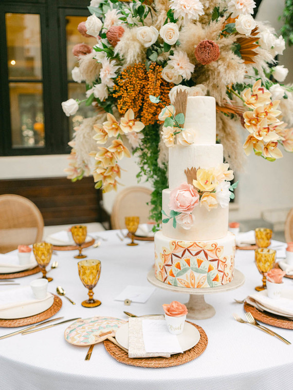 The wedding tablescape was done with lush florals and greenery, wicker chargers and amber glasses