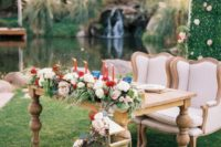 10 a chic and luxurious sweetheart table with bright blooms, red candles and refined chairs