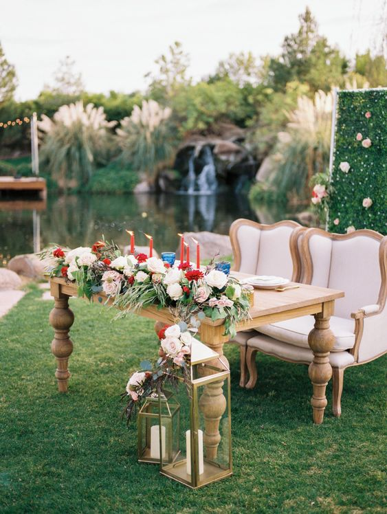 a chic and luxurious sweetheart table with bright blooms, red candles and refined chairs