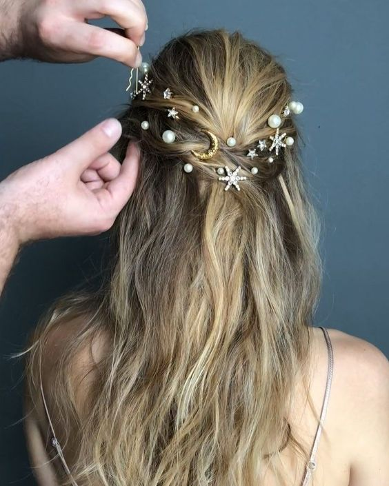 a messy twisted half updo with silver rhinestone stars and small and large pearl hair pins are two trends in one