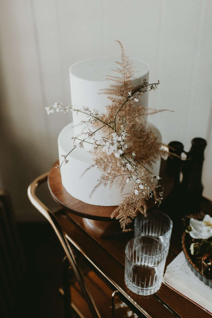 The cake was white, with gold leaves and white blooming branches
