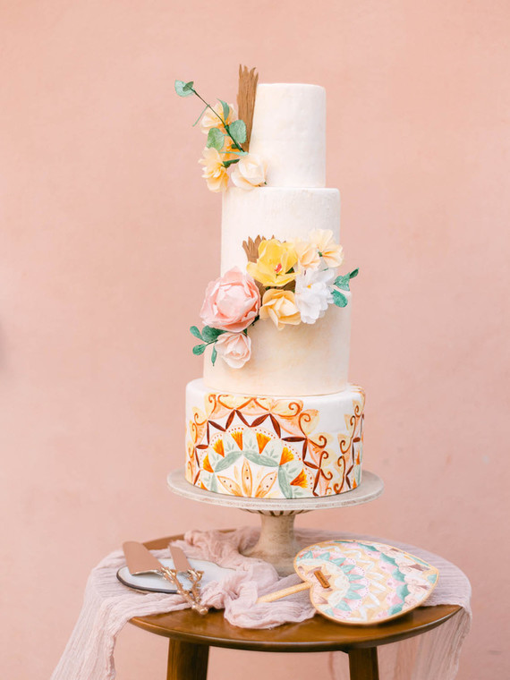 The wedding cake was white, with colorful painting and bright sugar and real blooms