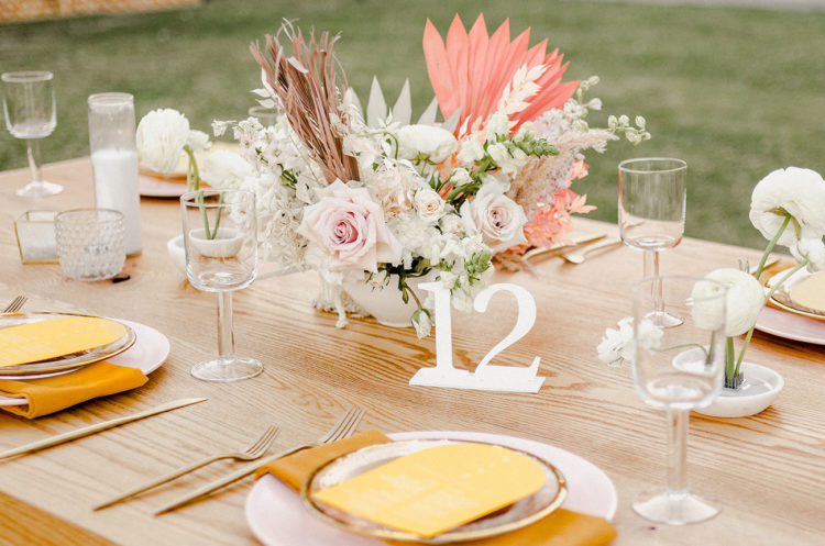 The wedding tablescape was done with blush blooms, pink fronds and mustard napkins