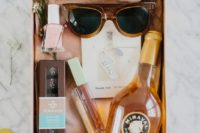 12 a chic bachelorette gift with some alcohol, chocolate, sunglasses, nail polish and some beauty products