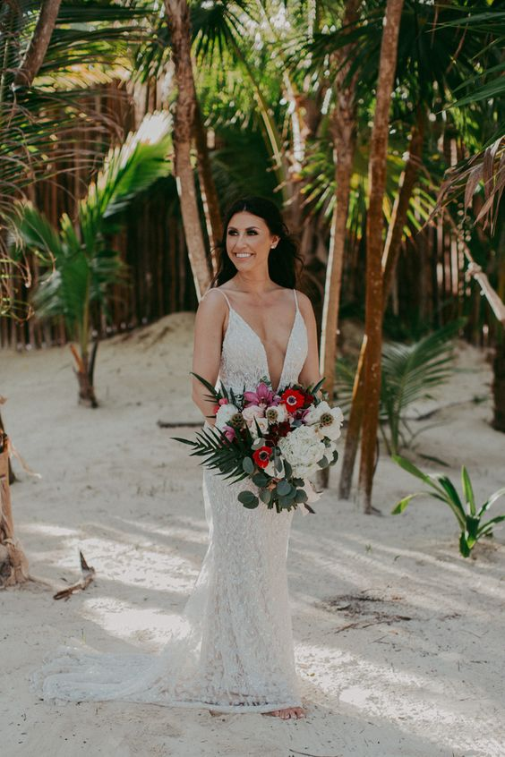 a lace embellished wedding dress with spaghetti straps, a train and a deep plunging neckline to breathe
