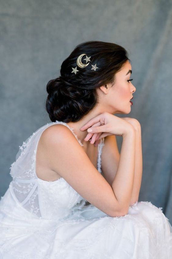 gold and rhinestone moon and star hair pins highlight this elegant low updo and make it celestial
