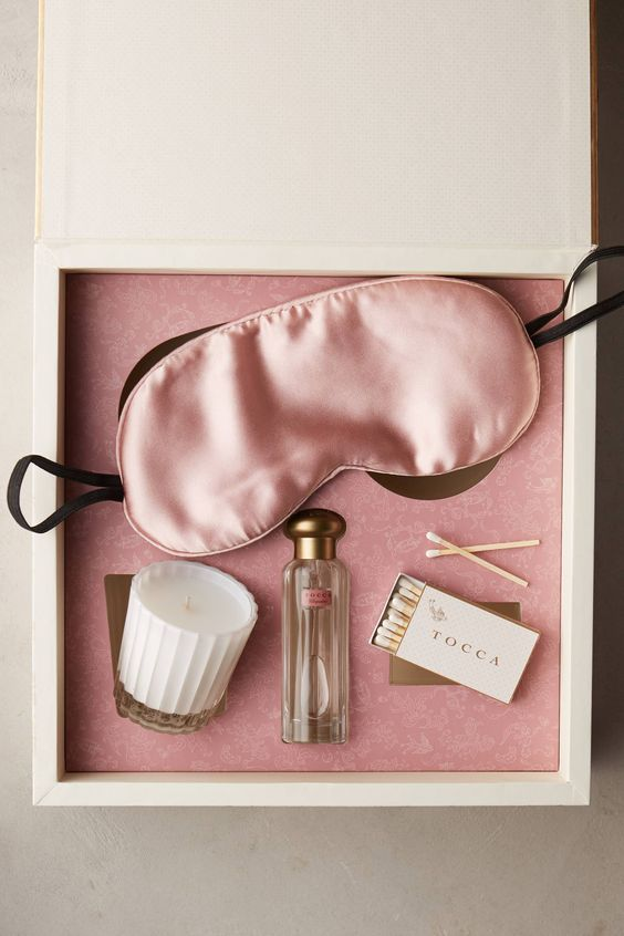 a simple and chic bachelorette box with a sleep mask, a candle, a perfume and matches