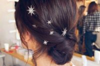 17 a stylish twisted low updo with silver and rhinstone star hair pins looks very edgy and very chic
