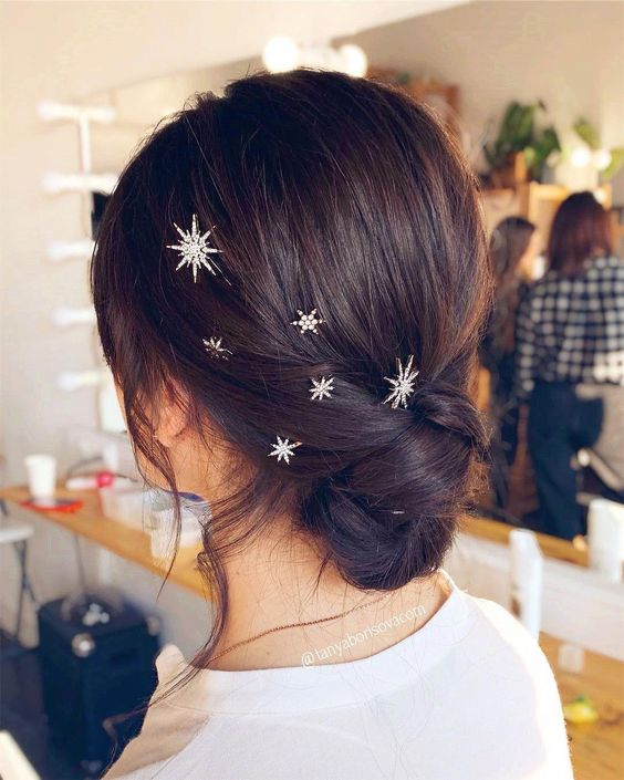 a stylish twisted low updo with silver and rhinstone star hair pins looks very edgy and very chic