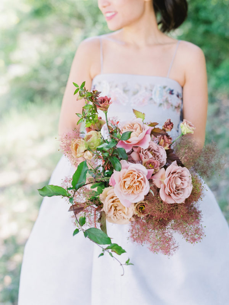 a beautiful and romantic wedding bouquet with pink and peachy roses, greenery and smoke bush looks trendy at the same time