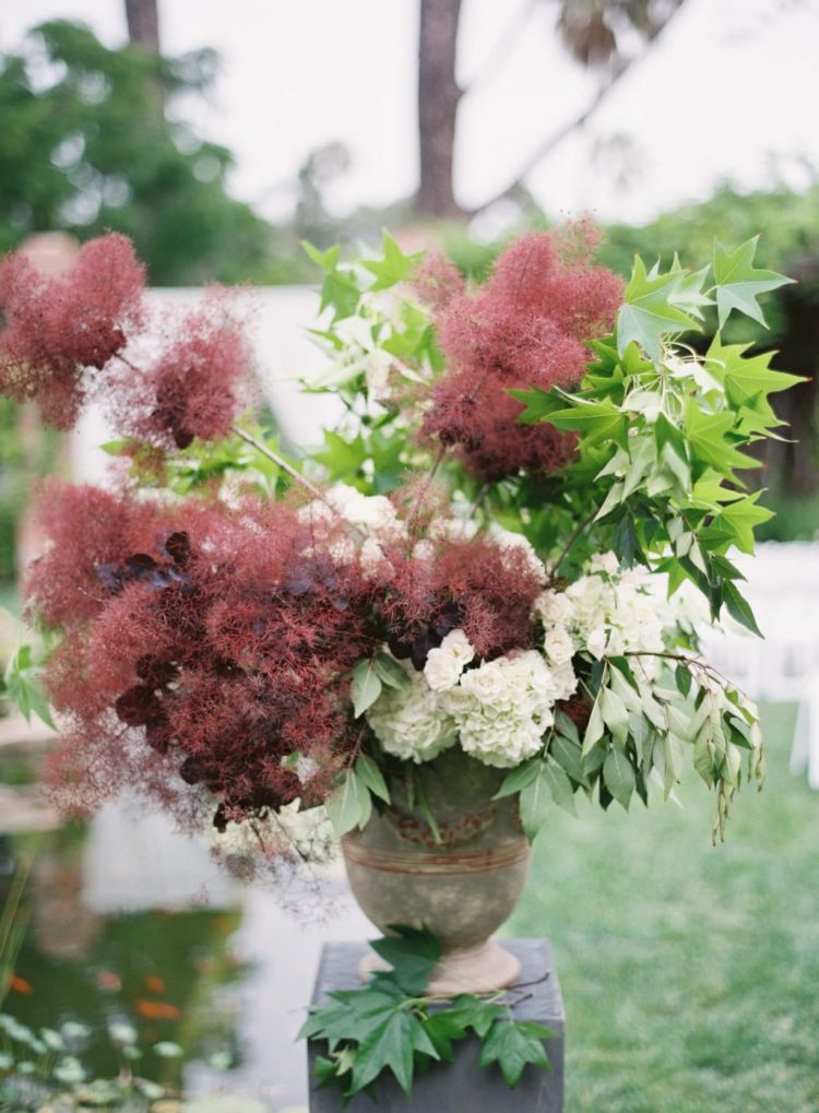 a beautiful wedding arrangement with burgundy smoke bush, dark leaves, greenery and white blooms looks refined