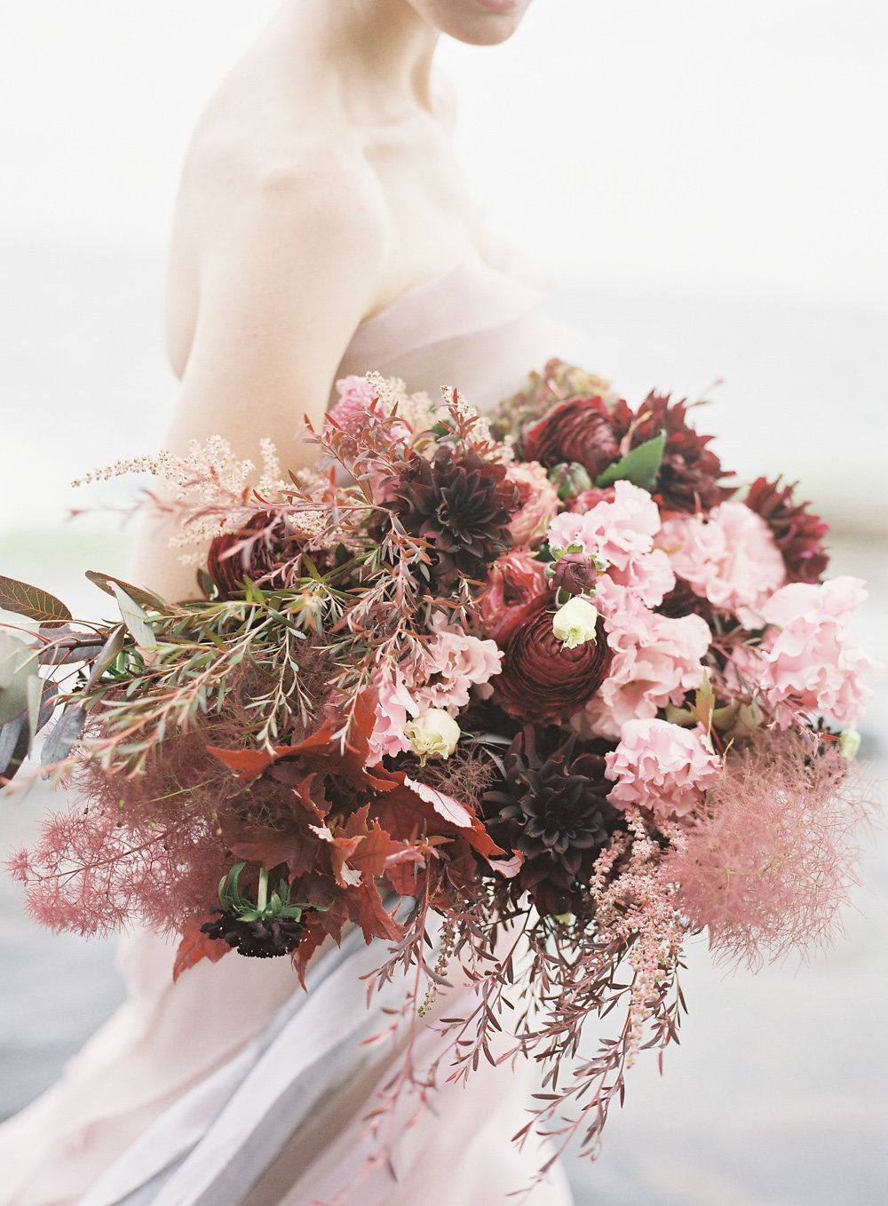 a bold wedding bouquet with smoke bush, burgundy ranunculus and other blooms in burgundy and pink
