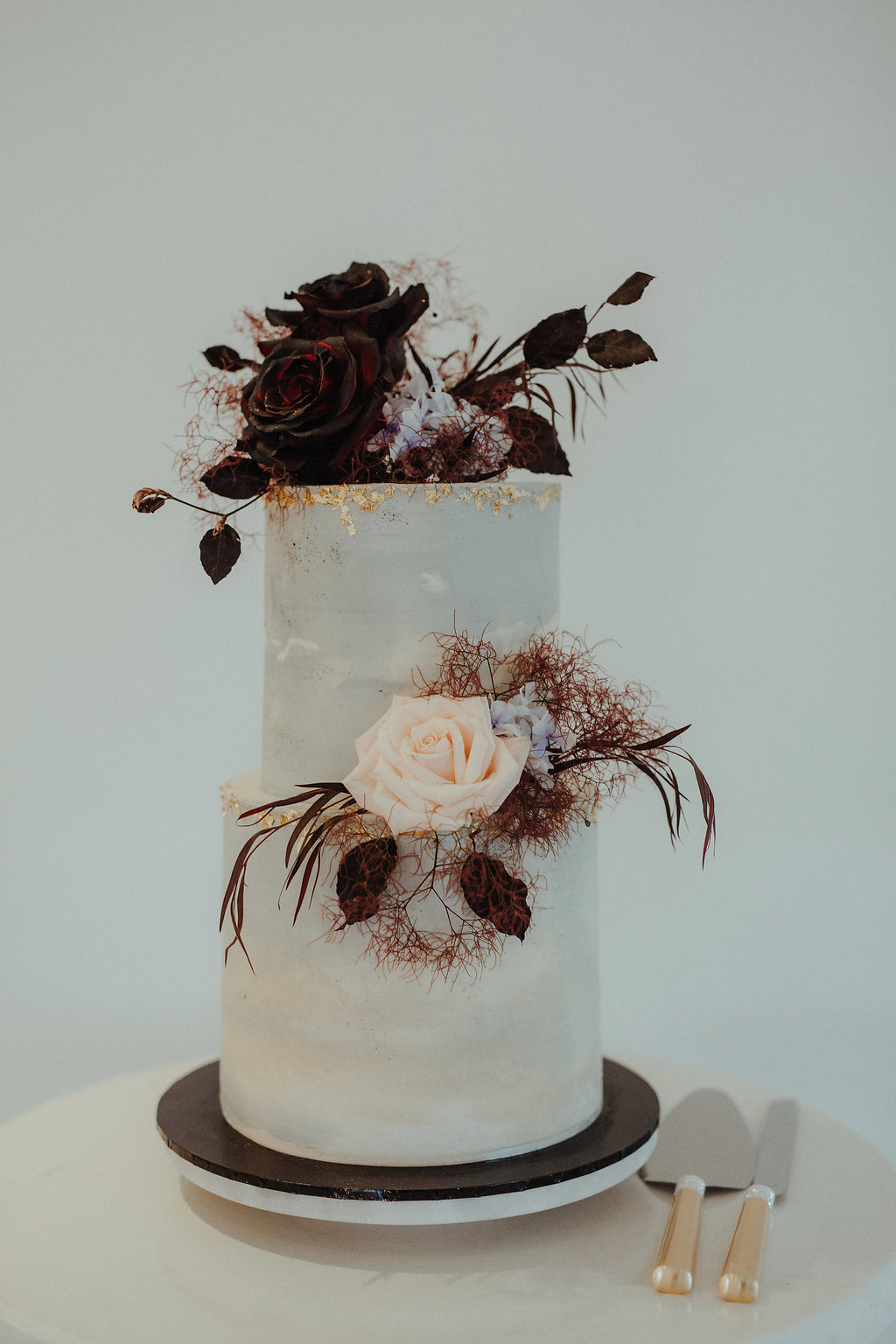 a chic wedding cake with gold leaf, dark and blush roses, leaves and smoke bush looks really unusual