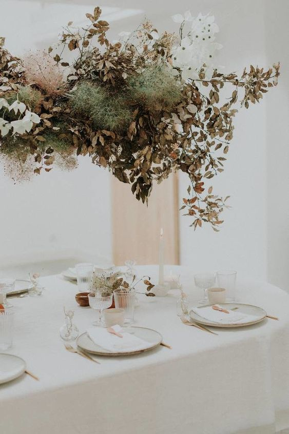 a decadent fall wedding overhead installation with white blooms, smoke bush and dried leaves for a fall wedding