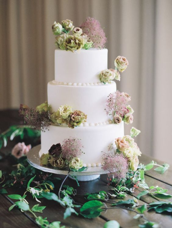 a delicate wedding cake in white decorated with green blooms and burgundy smoke bush