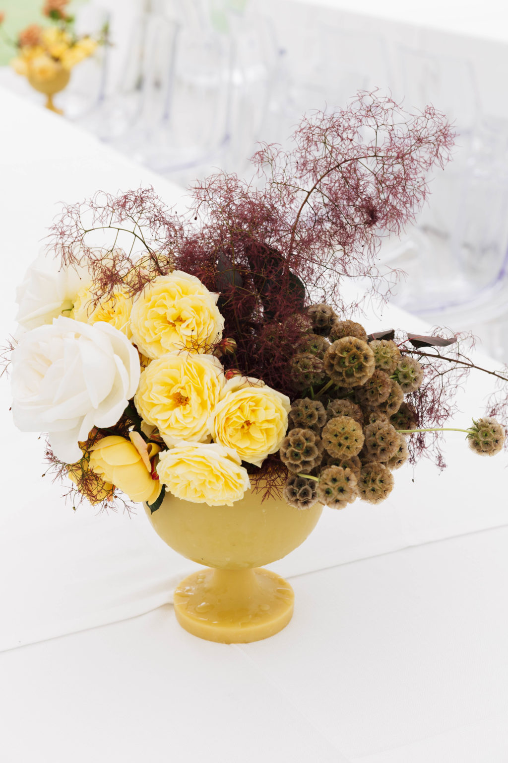a fall wedding centerpiece in green, white, yellow and burgundy smoke bush is a refined and decadent idea