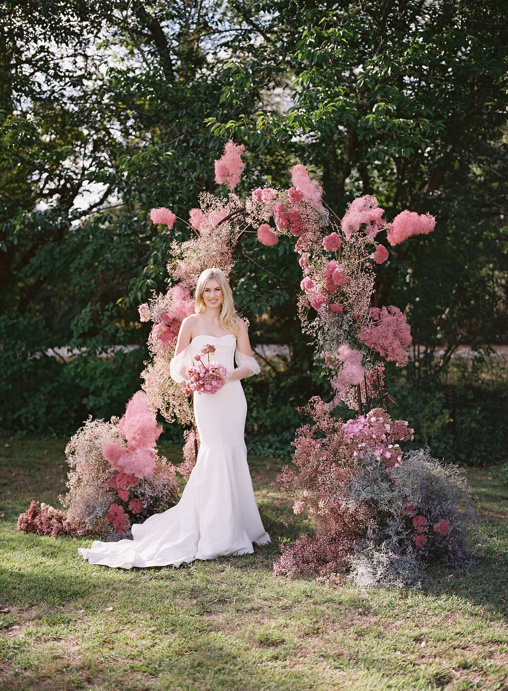 a gorgeous wedding arch done with delicate gypsophila and smoke bush in shades of pink just wows