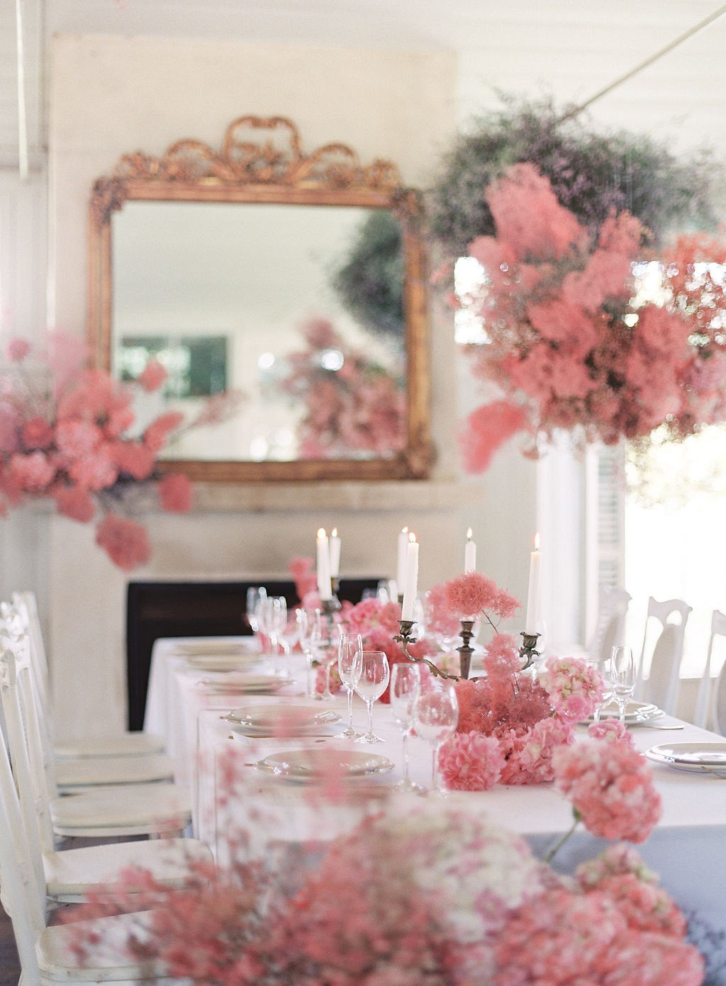 a refined wedding reception table with pink blooms and smoke bush on it and over it
