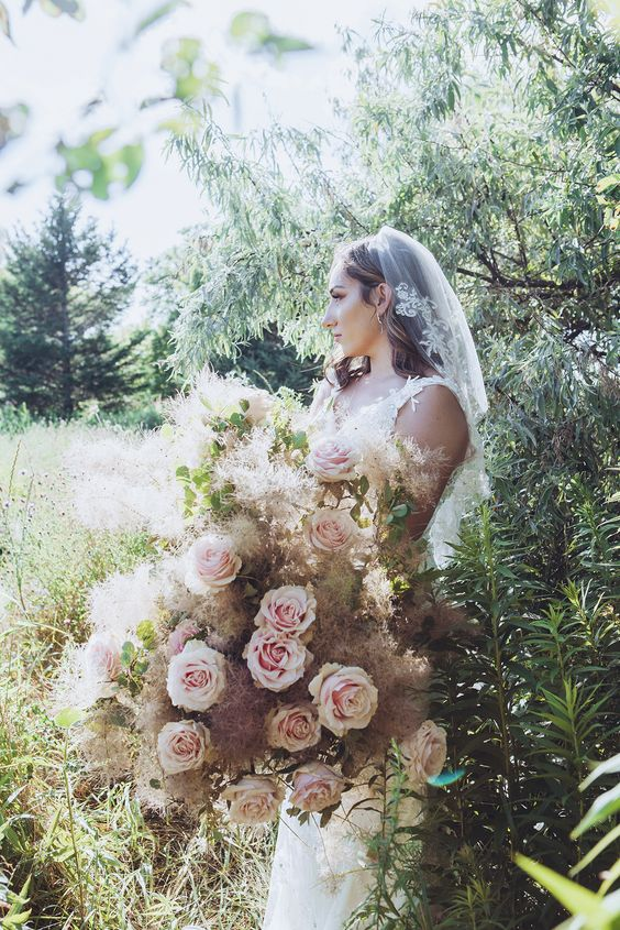 a unique oversized wedding bouquet with pink roses, greenery and smoke bush is a chic and romantic idea