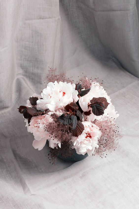 a wedding centerpiece with blush blooms, dark leaves and smoke bush is a creative and very bold idea