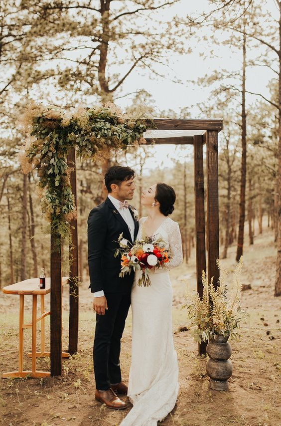 a woodland wedding arch with greenery, ferns and smoke bush is a unique idea for a strong natural feel