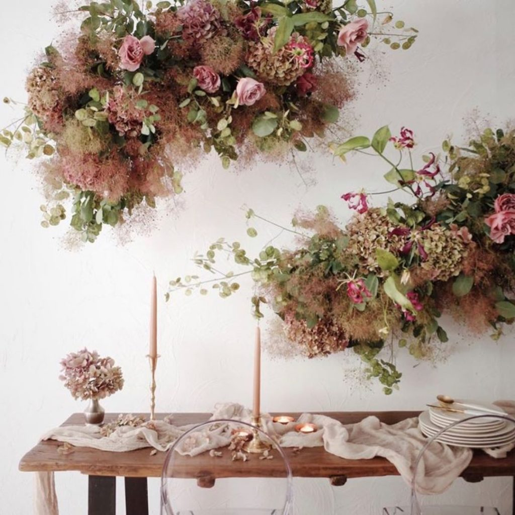 exuberant arrangements with smoke bush, greenery and pink roses make the space very chic and very refined