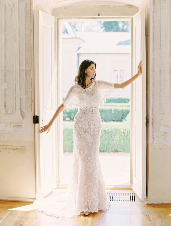 The bride was wearing a beautiful lace fitting wedding dress with a train and a gorgeous cape