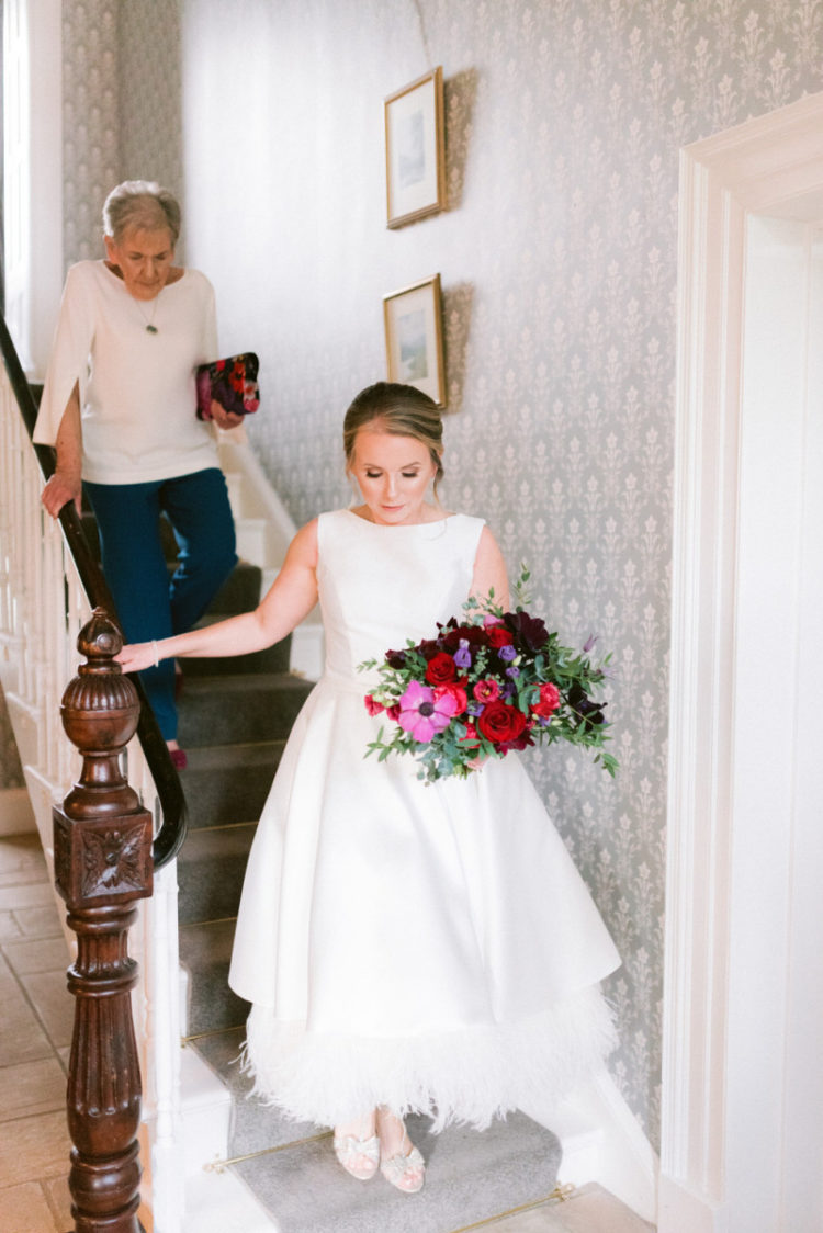 The bride was wearing a lovely a-line tea-length wedding dress with ostrich feathers and sparkly wedding shoes