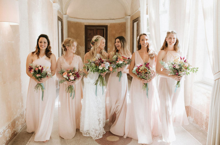 The bridesmaids were wearign mismatching blush maxi dresses and carrying bright bouquets