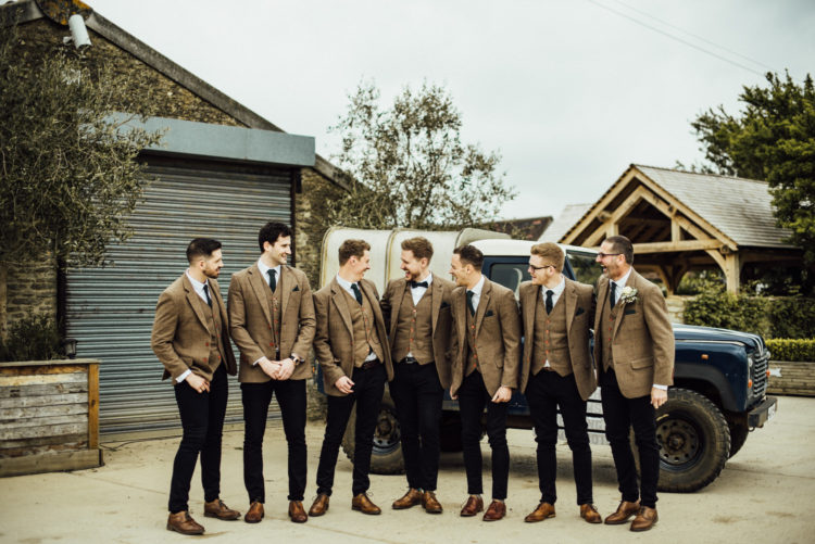 The groom and groomsmen were wearing tan tweed blazers and waistcoats, black pants and shoes
