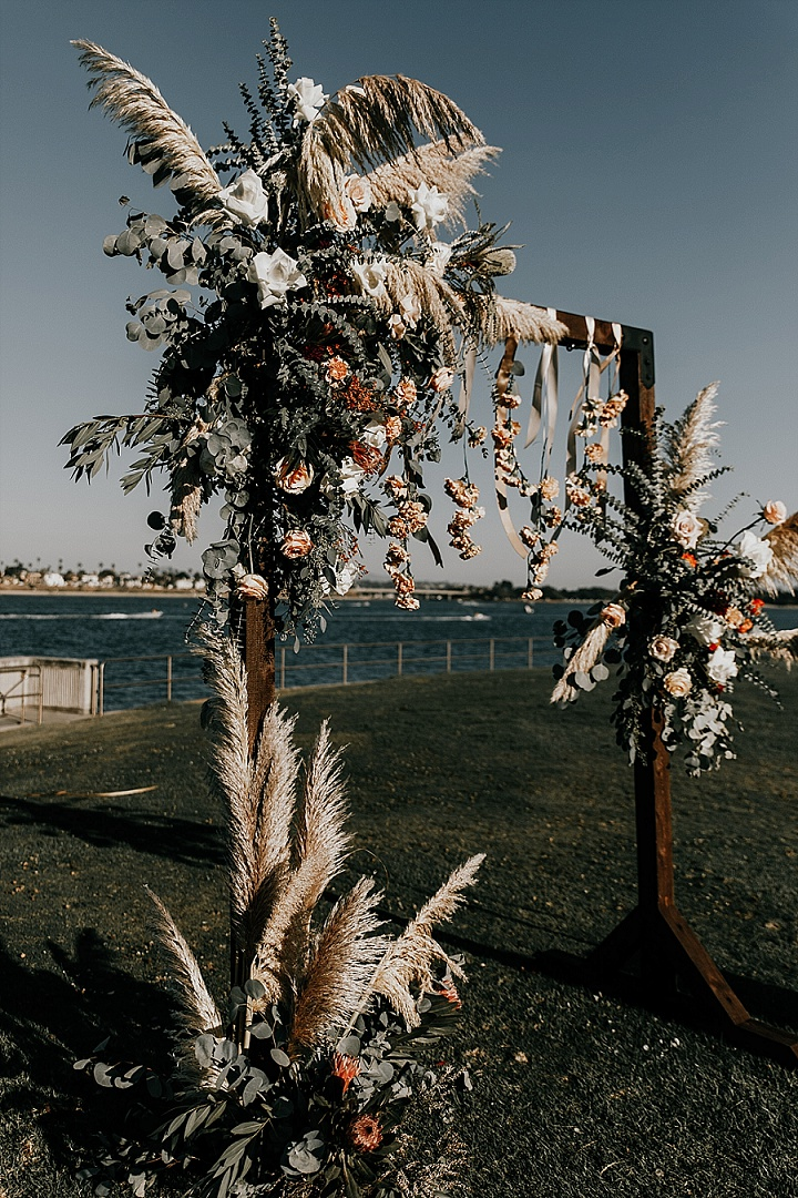The wedding arch was done with pampas grass, neutral and pastel blooms, greenery and leaves