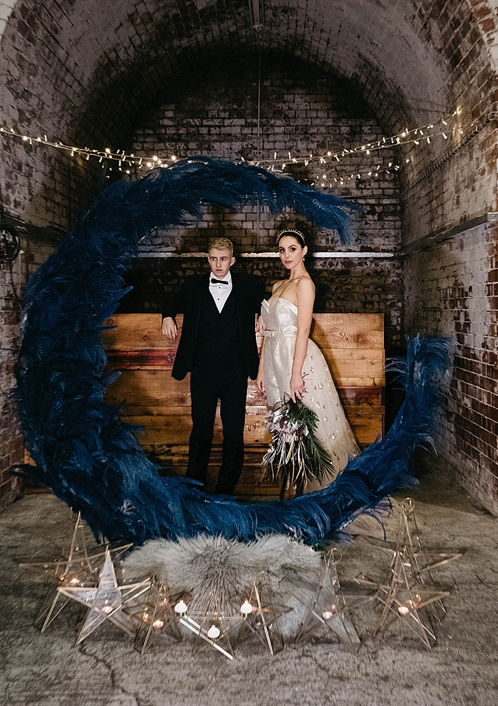 The wedding backdrop was done with blue feathers, star-shaped candle lanterns
