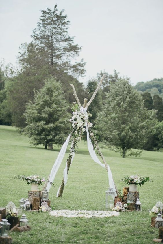 a boho wedding arch - a teepee with white fabric, greenery and white blooms, with florals and candle lanterns around