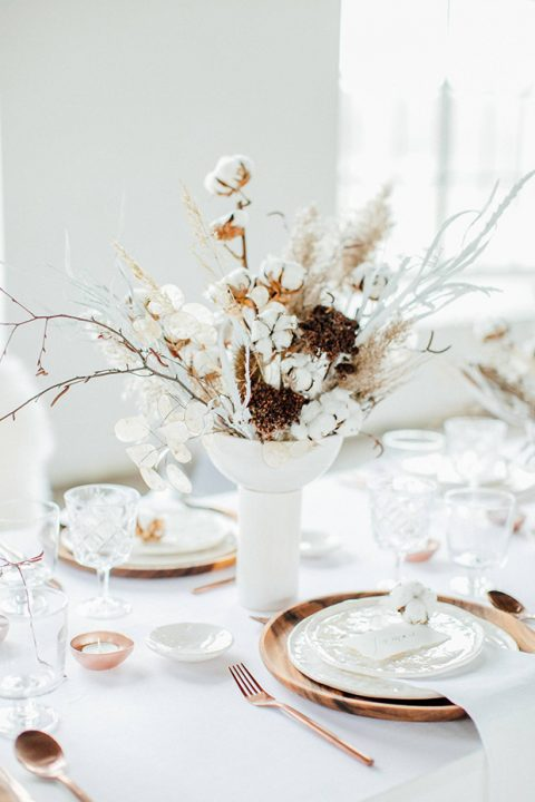 a textural wedding centerpiece of cotton branches, lunaria, branches and some dried berry branches
