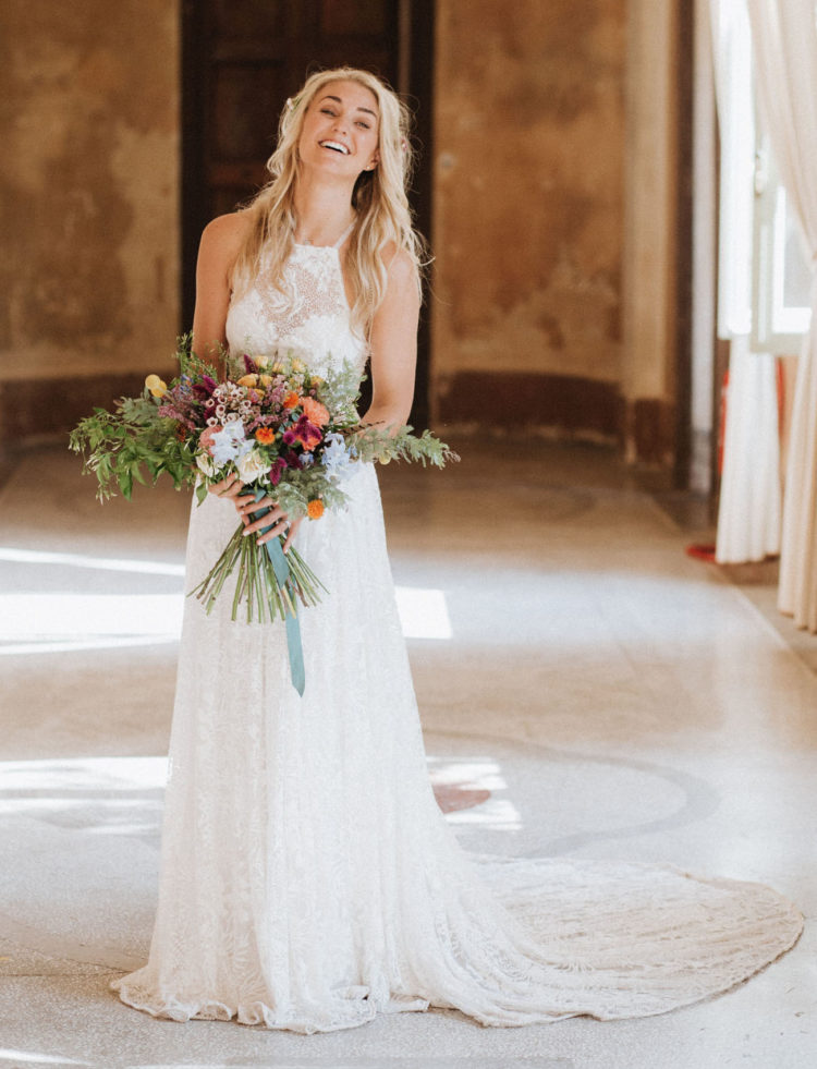 The bride was rocking a lace halter neckline and train wedding dress and carrying a bold bouquet