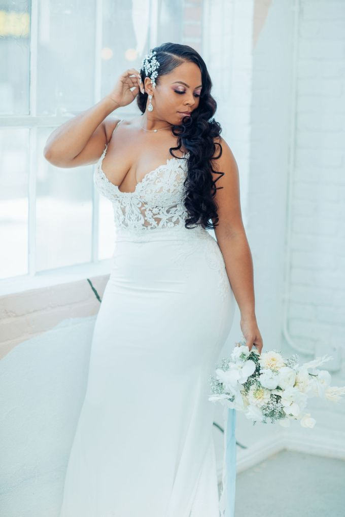 The bride was wearing a modern wedding gown with a lace embellished bodice with a deep neckline and a plain skirt