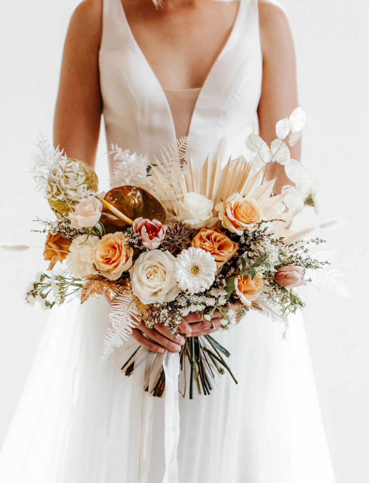 The wedding bouquet was done with peachy and pink blooms, fronds, greenery and lots of catchy details