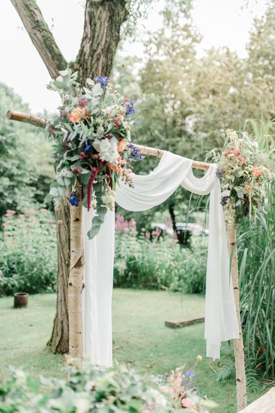a relaxed backyard wedding arch of wood, airy white fabric, colorful blooms and wildflowers and greenery for a boho wedding