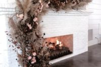 03 a wedding floral installation of pampas grass, blush blooms, dried branches over the fireplace