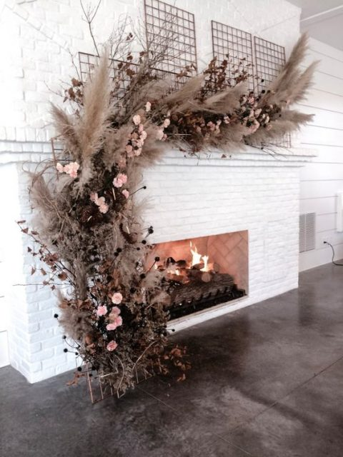 a wedding floral installation of pampas grass, blush blooms, dried branches over the fireplace