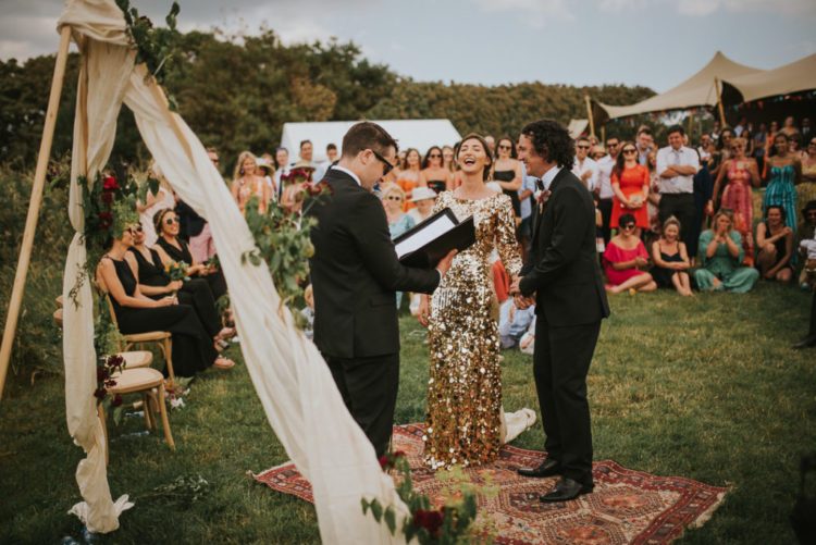 Everyone gathered in the back seaside garden and the ceremony space was done with a boho rug, greenery and some blooms