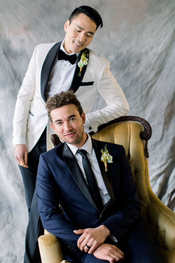 One groom was wearing a white tux with black lapels, and the second one was wearing a navy one