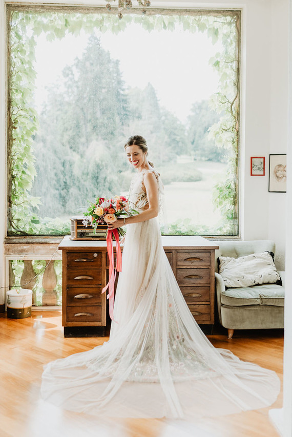The bride was wearing a gorgeous floral layered wedding dress with a train