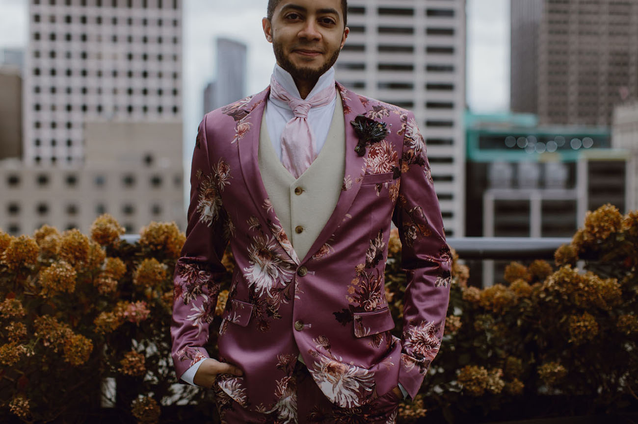 The groom was wearing a pink floral suit, a creamy waistcoat, a pink tie